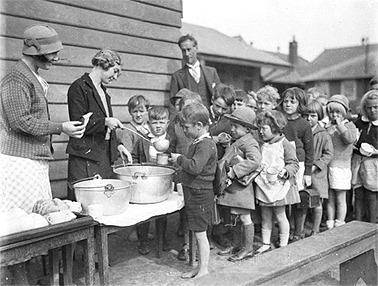 HChildren line up fro a free issue of soup and bread during the