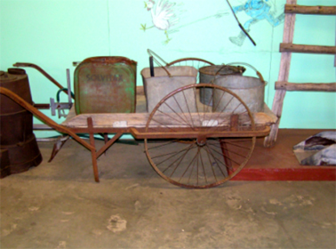 Farm wheel barrow with bucket and cans c.1920 - 30s, Photograph Wollondilly Heritage Centre