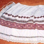 "Kate: ""The apron is white cotton with rows of coloured cross-stich patterns embroidered on it and a broderie Anglaise border. I think my mother [Anna] took it with her when she was deported by the Germans from the Ukraine and sent to work in Austria."""