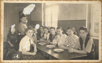Maria Cebulski with other young Polish women transferred to work in Germany by Nazis. Maria is seated third from left, directly under the window.