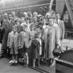 """I have a group photo of the family taken before we went aboard and my little brother Peter can be seen holding my little doll that I brought with me and still have."""