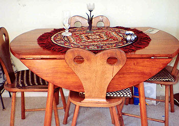 """My husband Ted made this small, round dining table with four matching chairs with heart-shaped backs in a European style with leaves on the table so it could be extended. He had to make it quickly because we were loaned a table and the people were moving to Melbourne and wanted it back."""