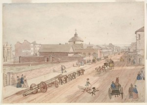 Hand-coloured photographic print after a John Rae watercolour, showing a view north along George Street, c.1840s. The Old Sydney Burial Ground cam be seen to the left of the picture, enclosed by a tall brick wall. A range of memorials are depicted: altar tombs, ledger stones and headstones. Courtesy State Library of New South Wales