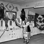"A Ukraine woman displays clothing at the ""New Australian's Handicrafts"" exhibition at Bathurst Migrant Camp c.1951. Courtesy National Archives of Australia"