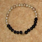 This is a [baby] bracelet somebody gifted [my son]. It is made of silver, white and black beads.